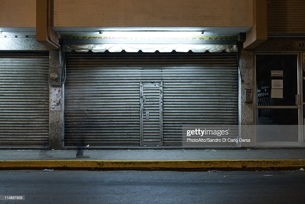 Store front with locked roll-up door at night : Stock Photo