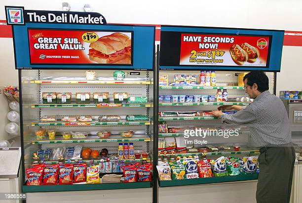 Store manager Bihari Sheth stocks items at the Deli Market inside a 7Eleven store May 9 2003 in Des Plaines Illinois Dallas Texasbased 7Eleven Inc...