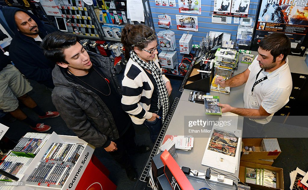 Store manager Brandon Khan (R) sells copies of 'Call of Duty: Ghosts' during a launch event for the highly anticipated video game at a GameStop Corp. store on November 5, 2013 in North Las Vegas, Nevada. Video game publisher Activision released the 10th installment in the 'Call of Duty' franchise at midnight.