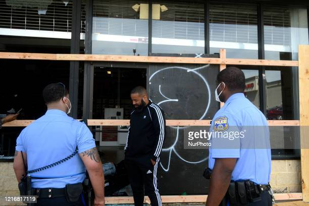 Store manager Mario Lawrence of Philadelphia talks to Police Officers outside the vandalized and looted Villa sneaker store in the Mt Airy/Wadsworth...