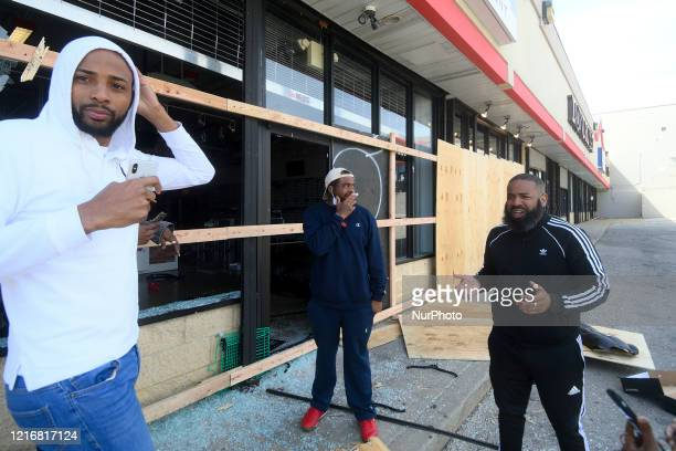 Store manager Mario Lawrence of Philadelphia talks with concerned community members outside a vandalized and looted Villa sneaker store in the Mt...