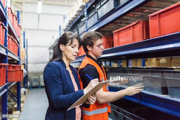 Store manager with warehouse worker checking stock levels