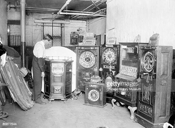 A store of confiscated illegal slot machines in a storage area in Chicago Illinois 1906 A man is looking at one of the slot machines From the Chicago...