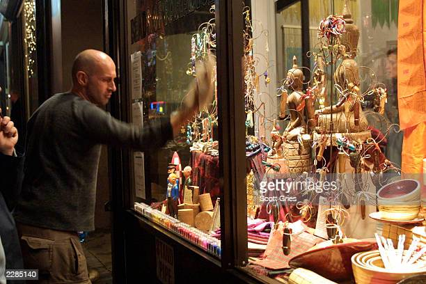 Store owner Brian Kenner washes the window in front of a christmas tree decorated with hand carved penises at 'Beads Of Paradise' in New York City...