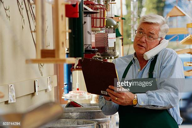 Store Owner Making Sale on Telephone