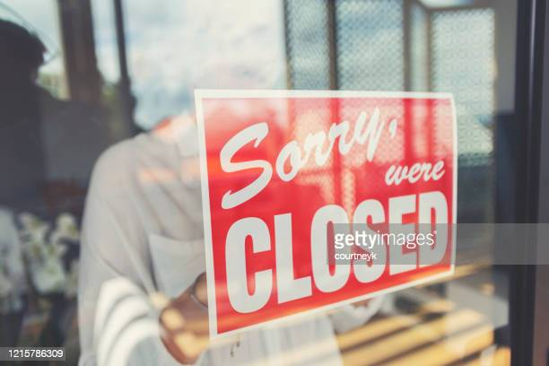 store owner putting up a closed sign in the window. - closed stock pictures, royalty-free photos & images