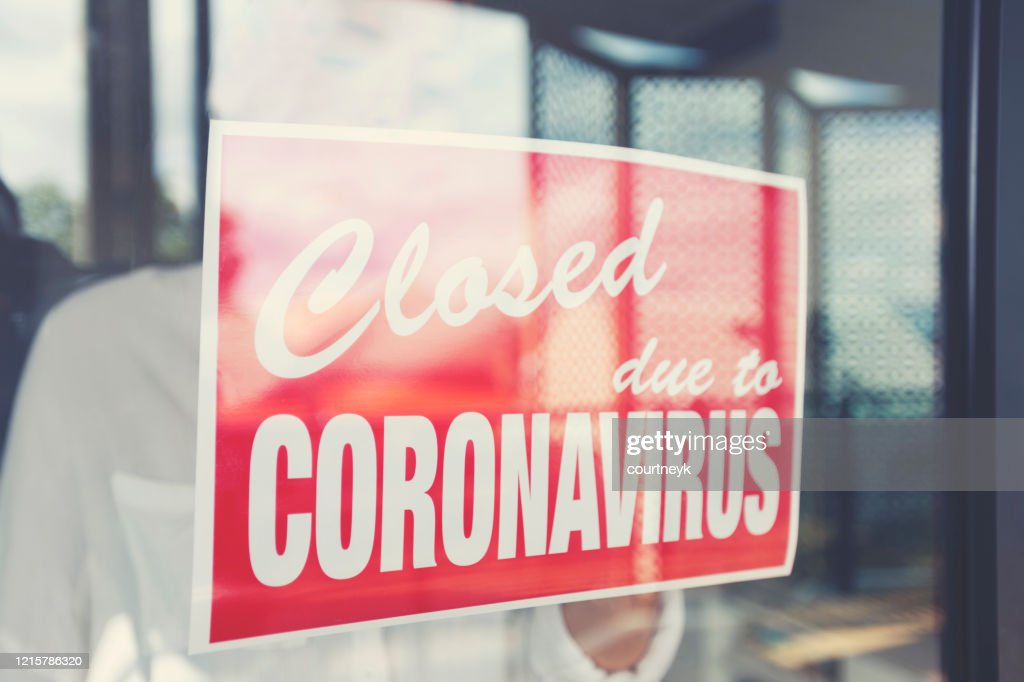 Store owner putting up a closed sign in the window : Stock Photo