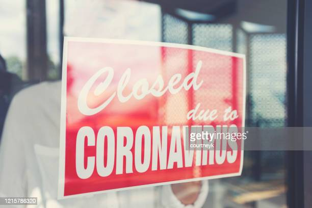 store owner putting up a closed sign in the window - cartello chiuso foto e immagini stock