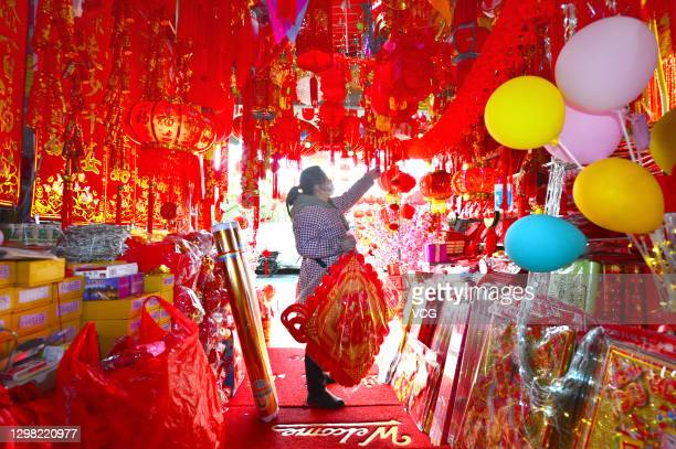 Store owner sells spring festival knots, lanterns, scrolls and other decorations before Chinese new year, on January 24, 2021 in Wuhan, Hubei...