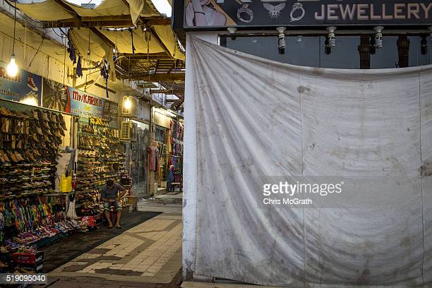 A store owner waits for customers behind a closed down store in the Old Market district on April 3 2016 in Sharm El Sheikh Egypt Prior to the Arab...