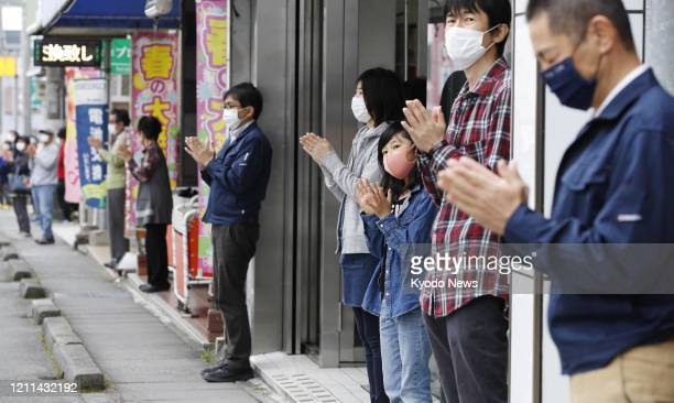 Store owners and shoppers, standing in front of shops in Susono in Shizuoka Prefecture, central Japan, on May 1 clap for a few minutes to thank...