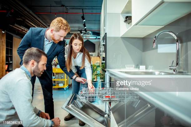 store salesperson demonstrating the features and functionality of a dishwasher to a young husband and wife in a kitchen equipment store - appliance stock pictures, royalty-free photos & images