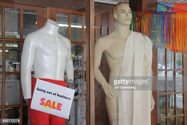 Store window display with naked mannequins with a going out of business sign