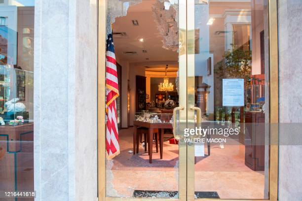 Store window is left broken after people looted it in the Grove shopping center in the Fairfax District of Los Angeles on May 30, 2020 following a...