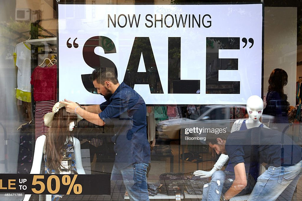 Store workers dress mannequins in front of a signage advertising a sale in the window of a clothing store in Cairo, Egypt, on Friday, Aug. 7, 2015. The Suez canal extension and other construction projects have boosted the economy, which grew above 4 percent in the nine months to March for the first time since 2010. Photographer: Shawn Baldwin/Bloomberg via Getty Images