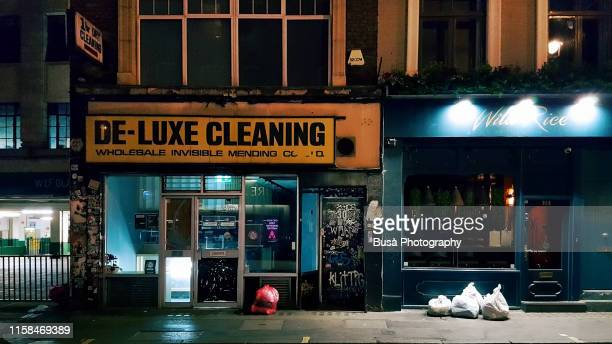storefront of dry cleaner in chinatown, in the city of westminster, london, england - run down stock pictures, royalty-free photos & images