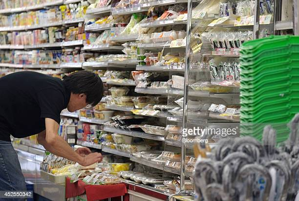 A storekeeper arranges products displayed at FamilyMart Co convenience store in Tokyo Japan on Wednesday July 23 2014 Japan suspended food imports...