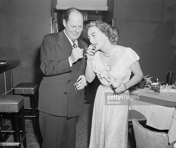 Stork Club Party for Joan Crawford New York New York Sherman Billingsley the perfect host lights a cigarette for Miss Joan Crawford at party in her...