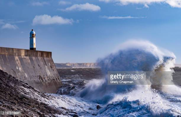 storm at porthcawl lighthouse - cliff stock pictures, royalty-free photos & images