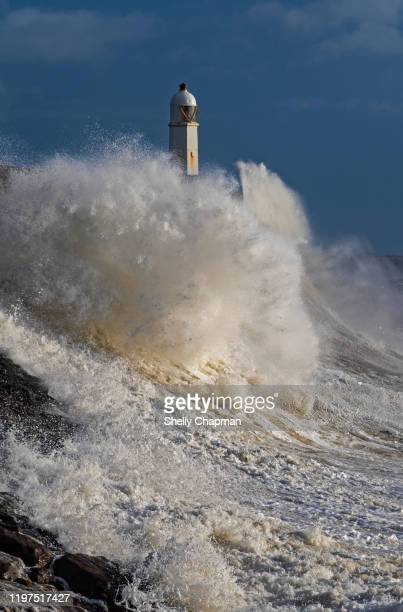 storm at porthcawl lighthouse - porthcawl stock pictures, royalty-free photos & images