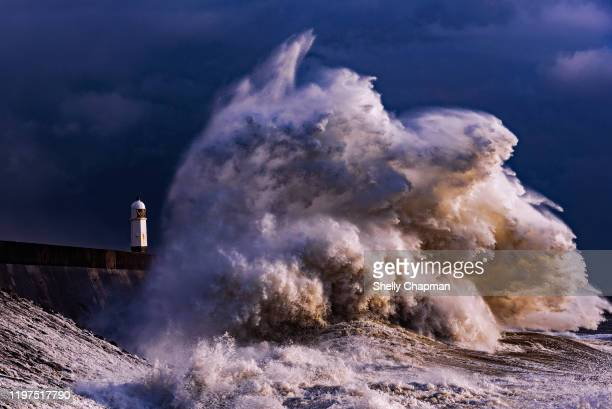 storm at porthcawl lighthouse - weather stock pictures, royalty-free photos & images