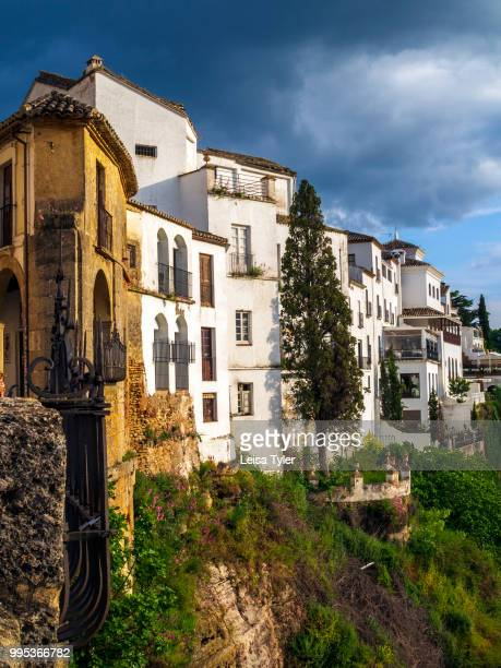 NUEVO RONDA ANDALUSIA SPAIN A storm brews over houses lining the El Tajo Gorge in Ronda a heritage town and popular tourist destination in Andalusia...