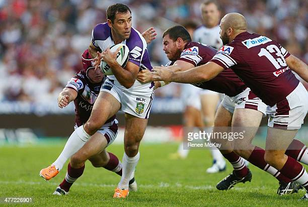 Storm captain Cameron Smith is tackled by Matt Ballin, Justin Horo and Glenn Stewart during the round one NRL match between the Manly Sea Eagles and...