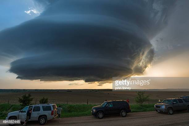 CONTENT] Storm chasers in 4x4 SUV cars on a dirt road with a massive mother ship shape storm cloud over the Great Plains of Nebraska at sunset