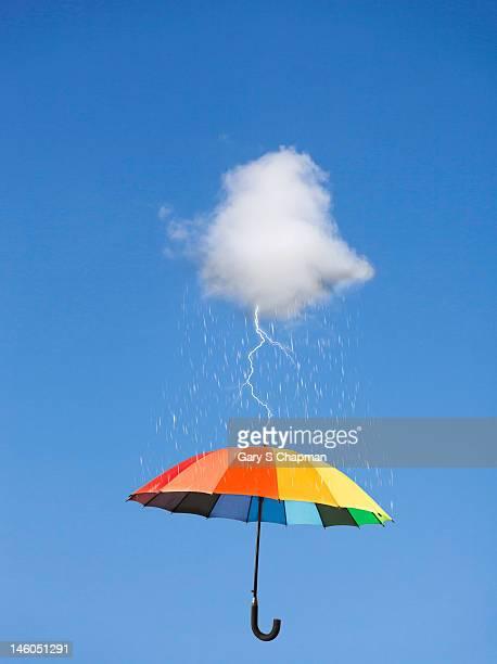 Storm cloud with lightning striking an umbrella