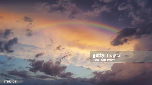 storm clouds and rainbow at sunset - rainbow stock pictures, royalty-free photos & images