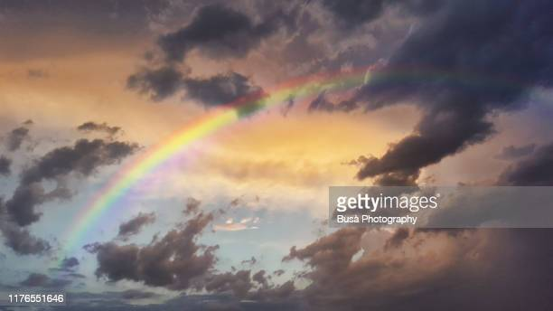 storm clouds and rainbow at sunset - speranza foto e immagini stock