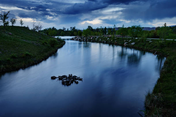 Storm clouds at dusk reflected in pond at Esther Simplot Park in Boise, Idaho, spring evening