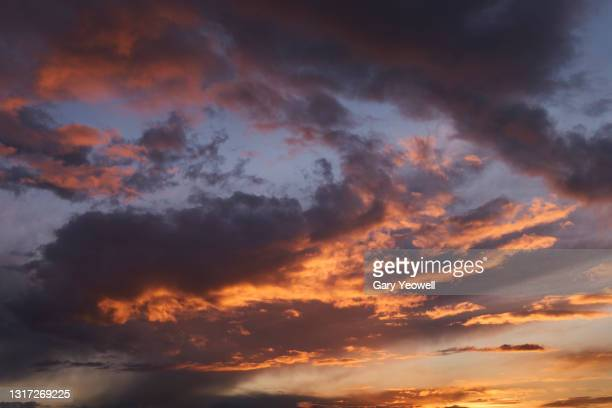 storm clouds at sunset - sunset stock pictures, royalty-free photos & images