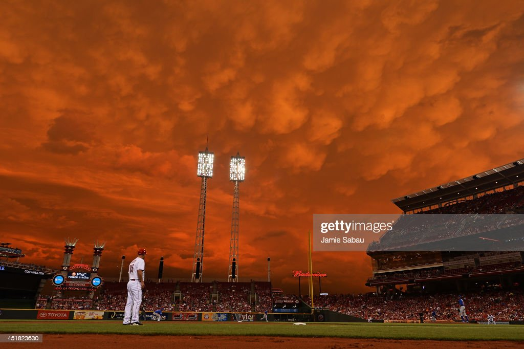 Storm clouds blanket the sky over Great American Ball Park as Starlin Castro #13 of the Chicago Cubs fields a ground ball in the fifth inning against the Cincinnati Reds as on July 7, 2014 in Cincinnati, Ohio. Cincinnati defeated Chicago 9-3.