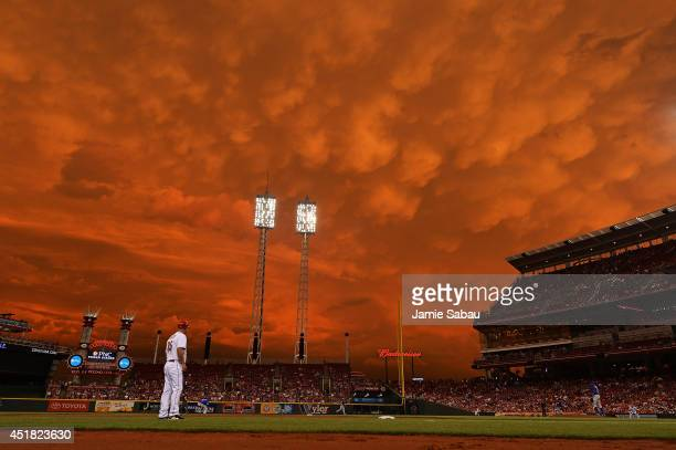 Storm clouds blanket the sky over Great American Ball Park as Starlin Castro of the Chicago Cubs fields a ground ball in the fifth inning against the...