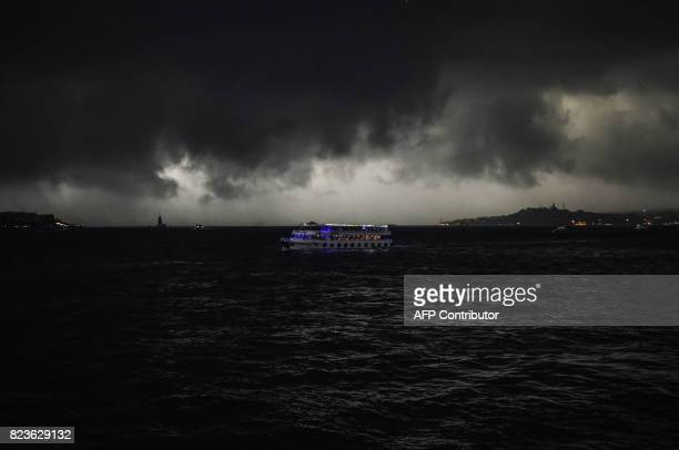 TOPSHOT Storm clouds gather over a ferry on the Bosphorus near Istanbul on July 27 2017 / AFP PHOTO / BULENT KILIC