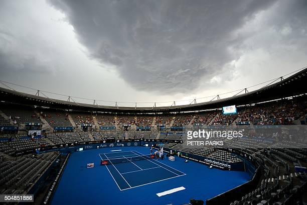Storm clouds gather over centre court as play is suspended during the Sydney International tennis tournament in Sydney on January 14, 2016. AFP PHOTO...