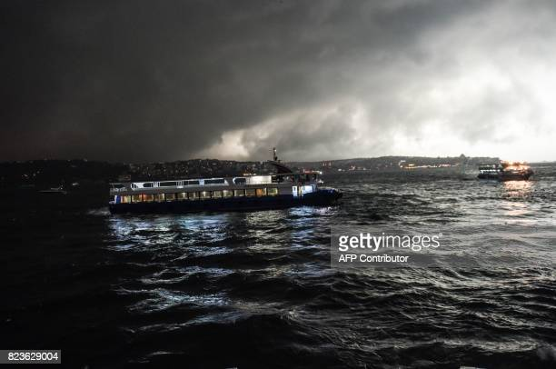 Storm clouds gather overhead as a ferry arrives at the port of Besiktas in Istanbul on July 27 2017 / AFP PHOTO / BULENT KILIC