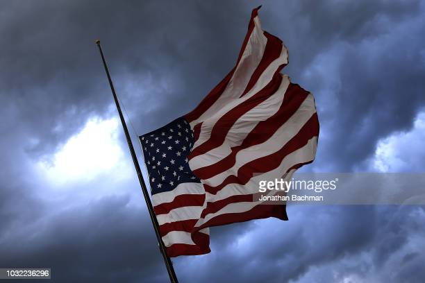 Storm clouds loom over an American flag at half mast before a game between the Mississippi State Bulldogs and the Stephen F Austin Lumberjacks at...