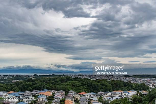 storm clouds on the residential district by the beach in kanagawa prefecture of japan - taro hama ストックフォトと画像