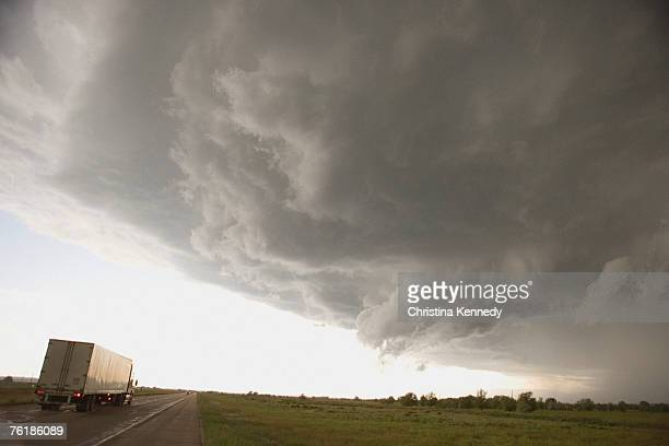 storm clouds over a rural landscape and a semi-truck on a highway - christina grosse stock-fotos und bilder