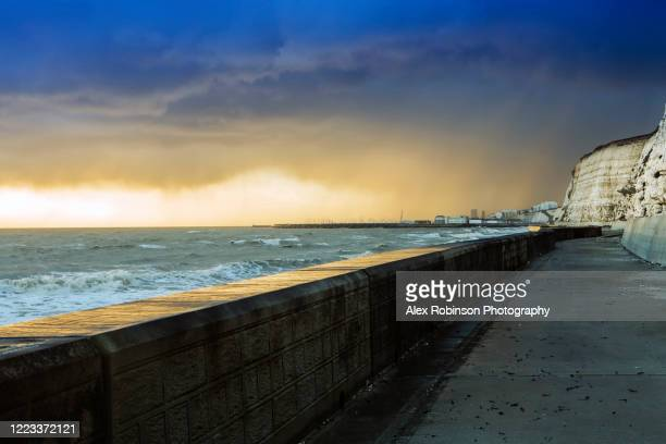 storm clouds over brighton town, peacehaven chalk cliffs and the english channel - イーストサセックス ストックフォトと画像