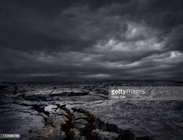 storm clouds over dry rocky landscape - volcanic rock stock pictures, royalty-free photos & images