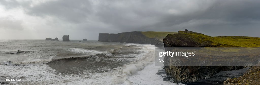 Storm clouds over Dyrholaey black basalt sand beach and cliffs : Stock Photo