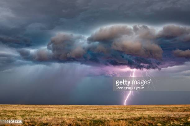 storm clouds over field - lightning stock pictures, royalty-free photos & images