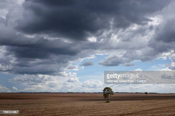 storm clouds over landscape against cloudy sky - matthias gaberthüel stock-fotos und bilder