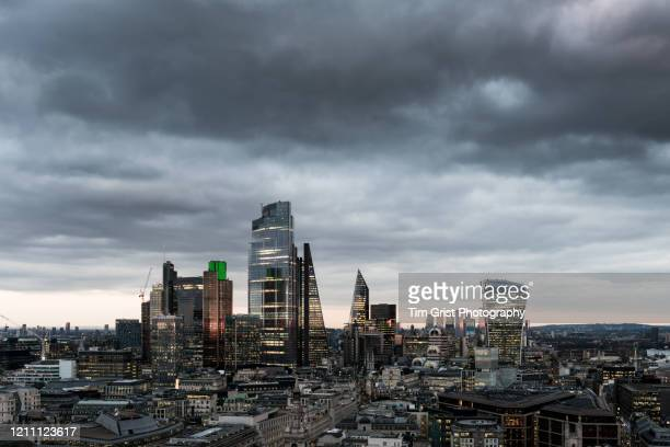 storm clouds over the city of london's financial district skyline - london skyline stock pictures, royalty-free photos & images