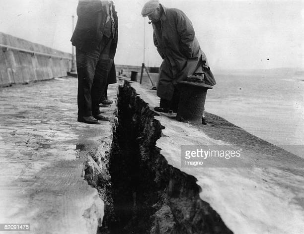 Storm damages in England man examining a crack in a mural England Photograph March 1st 1937 [Sturmschden in England Mnner begutachten den Riss in...
