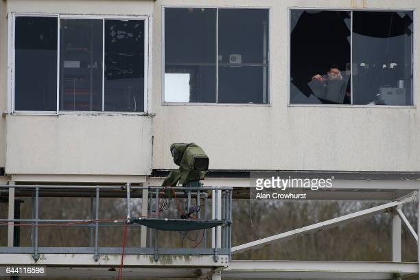 Storm Doris blows the window through in the commentators area of the officials box as a worker removes the pane of broken glass at Chelmsford...