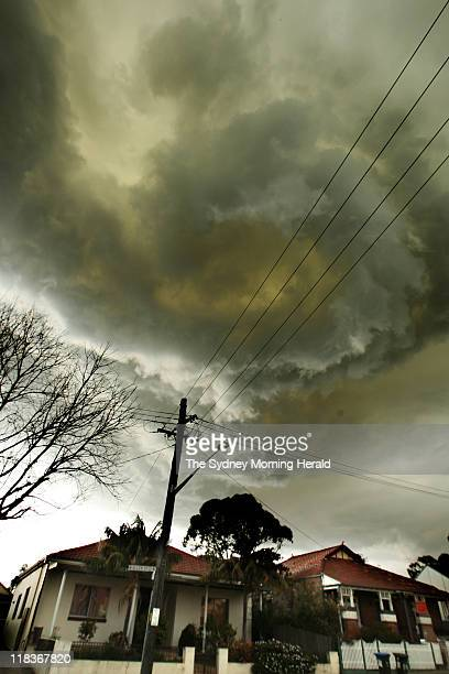 A storm front approaches Sydney from the north west as dark green and grey clouds hover over houses in Allen Street in the Sydney suburb of...
